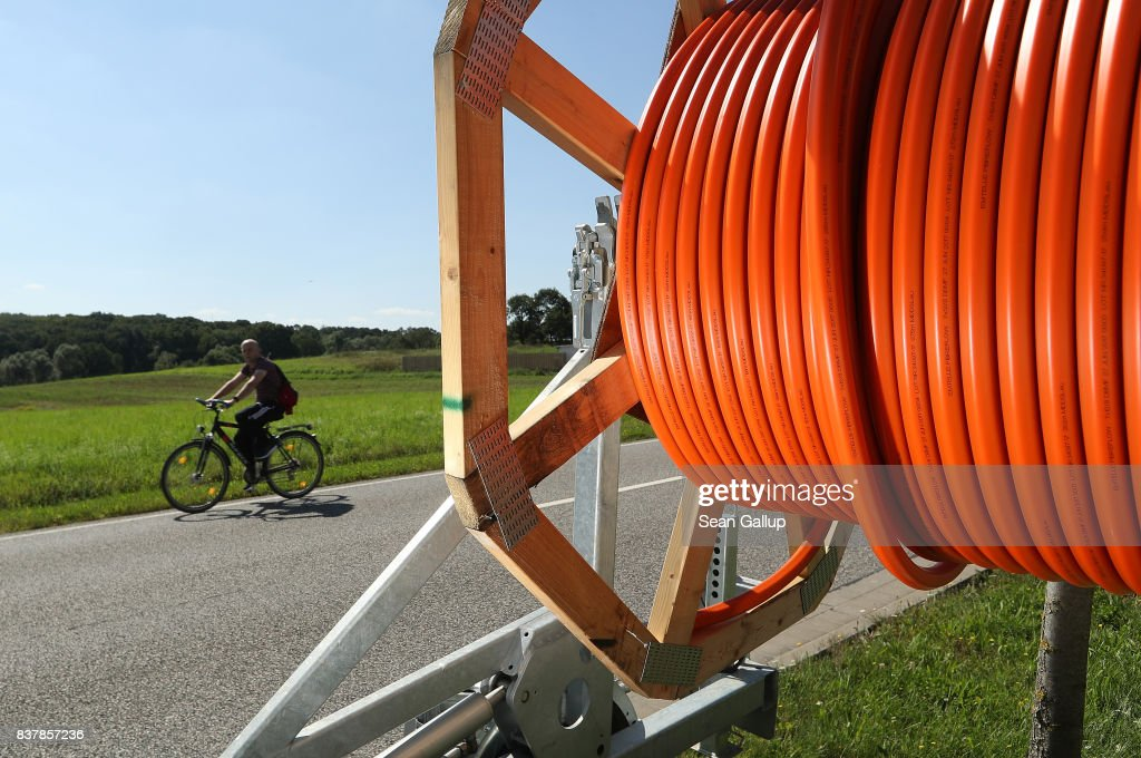 A man on a bicycle rides past a spool of tubing used for laying fiber optic cable underground during the installation of broadband infrastructure in the village of Bebertal by a private company called MDDSL on August 23, 2017 near Haldensleben, Germany. The German government is subsidizing efforts to improve broadband access in rural areas. Germany faces elections on September 24 and rural development is a strongly political issue. Many rural areas in Germany, especially in the eastern parts, are facing challenges, especially due to demographics.