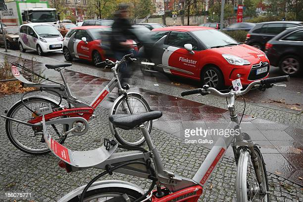 A man on a bicycle rides past cars operated by the Flinkster carsharing company and rental bicycles operated by Deutsche Bahn on October 28 2013 in...