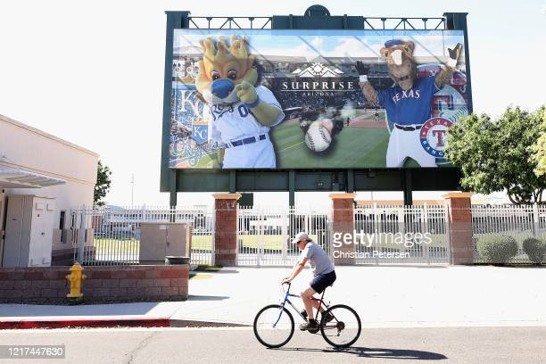 A man on a bicycle rides past the Texas Rangers and Kansas City Royals spring training facility Surprise Stadium on April 07 2020 in Surprise Arizona...