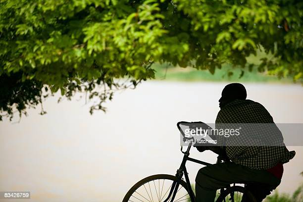 A man on a bicycle sits under a tree for shade next to the rapidly diminishing and polluted Lake Chad on July 10 2007 around Lake Chad Chad