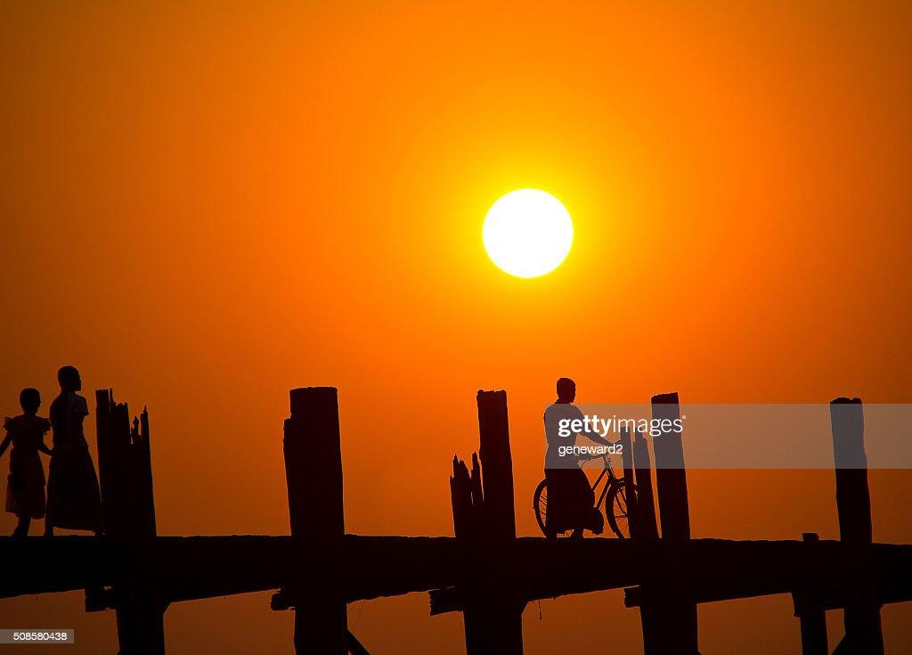 man on a bicycle stops on U Bein Bridge at sunset : Bildbanksbilder