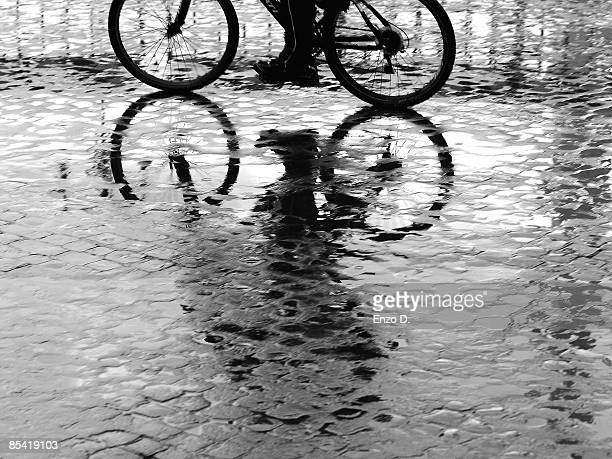 a man on a bike after the rain - cobblestone stock pictures, royalty-free photos & images