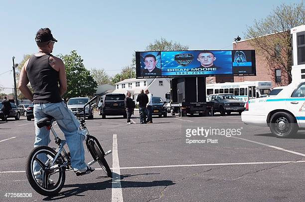 A man on a bike waits outside the funeral for NYPD Officer Brian Moore at St James Roman Catholic Church May 8 2015 in Seaford New York Officer Moore...