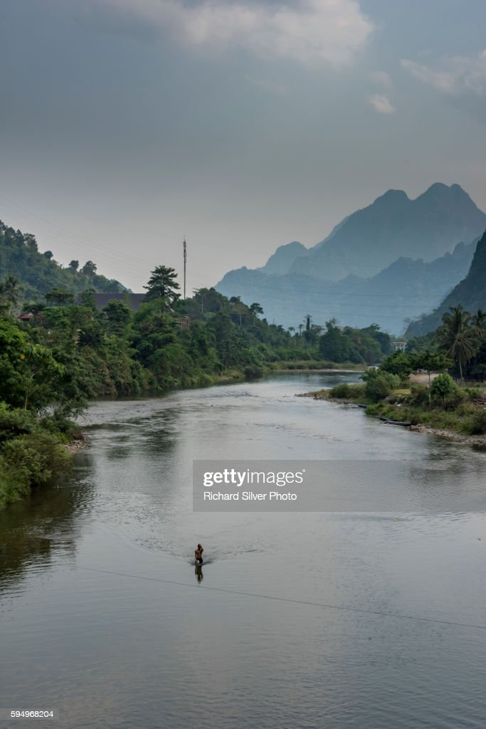 Man on a boat on a river with mountains in Vang Vieng, Laos : Stock Photo