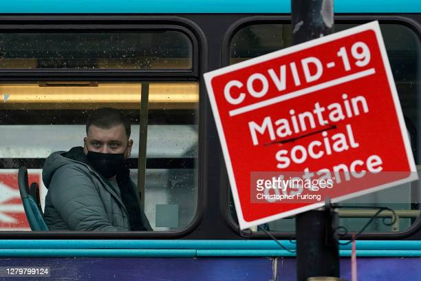 Man on a bus wears Covid-19 protective face on October 12, 2020 in Liverpool, England. Under a new three-tier system, English cities will be subject...