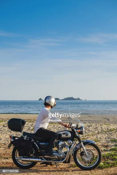 Man on a classic motorcycle looking at the sea