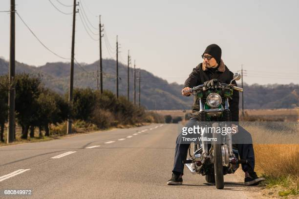 A man on a custom motorcycle taking a rest on the side of a desert road