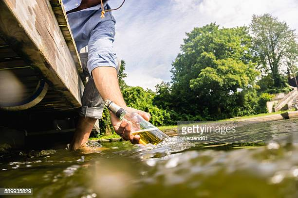 Man on a house boat cooling bottle of beer in water