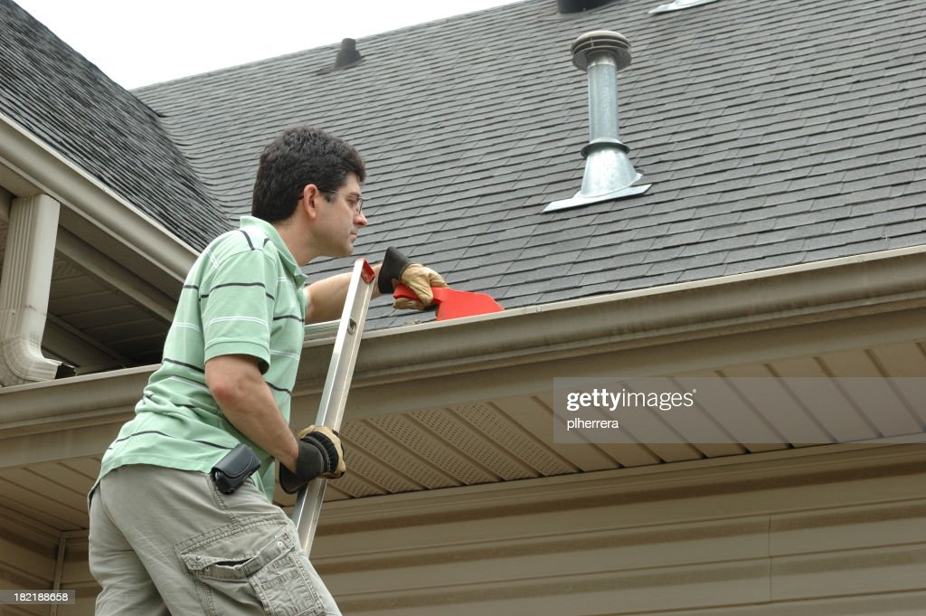 Man on a Ladder Cleaning Leaves from Gutter : Stock Photo
