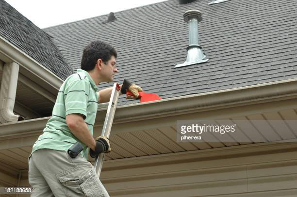Man on a Ladder Cleaning Leaves from Gutter