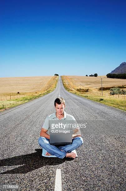 Un homme sur un ordinateur portable dans le milieu de la route