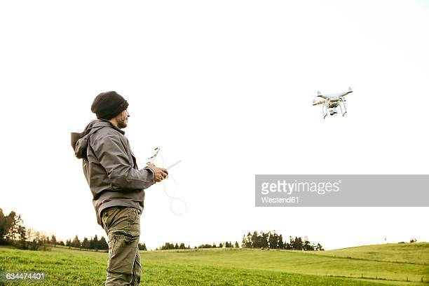 Man on a meadow flying drone