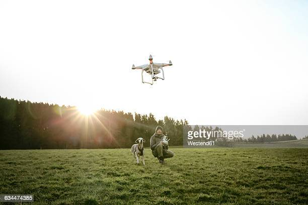 Man on a meadow flying drone while his dog watching