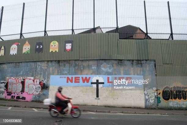 A man on a motorbike goes past a mural with a cross promising a NEW LIFE painted under the high wall and fences of the Catholic side of the Cupar Way...