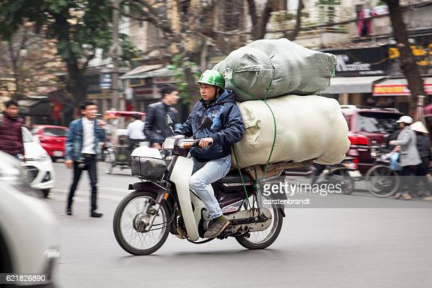 man on a motorbike with two big sacks - capital cities stock photos and pictures