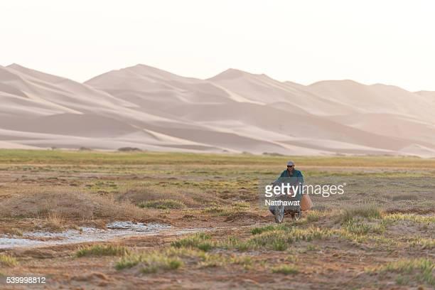A Man on a motorcycle, Khongoryn Els Sand Dunes, Gobi Desert, Mongolia.