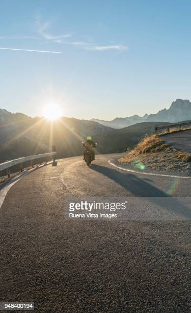 Man on a motorcycle on a mountain road at sunset