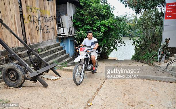 A man on a motorcycle passes by a soldier near the river in La Macerena Meta department Colombia on February 24 2016 Between 1998 and 2002 during the...