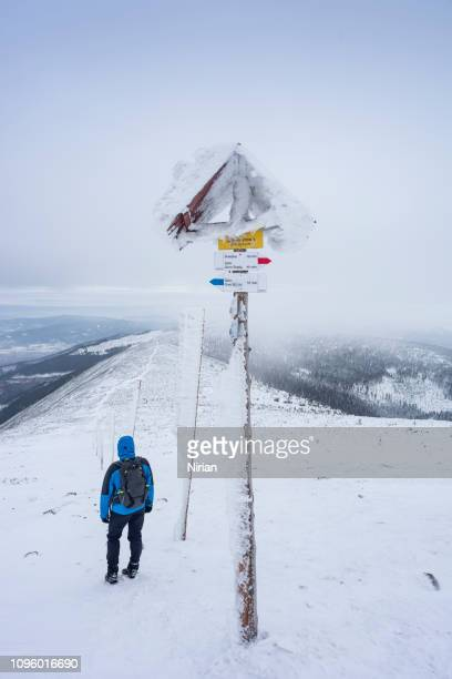 a man on a mountain trail next to a touristic indicator, all covered in snow - bohemia czech republic stock pictures, royalty-free photos & images