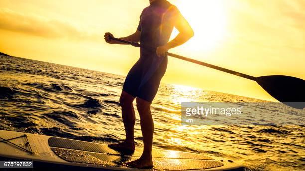 日没前に paddleboard の男