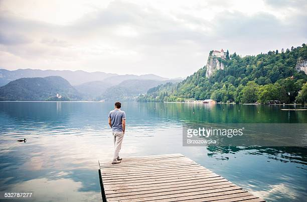 Man on a pier admiring view of lake (Bled, Slovenia)