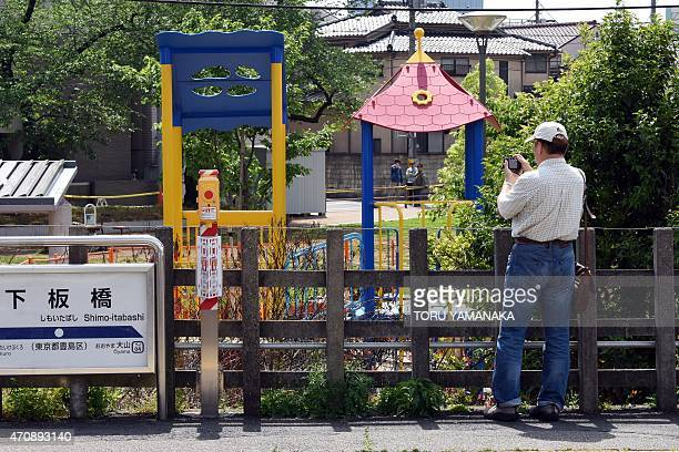A man on a platform takes pictures of a slide surrounded by fences at a playground in Tokyo on April 24 2015 Soil underneath the slide at the park in...