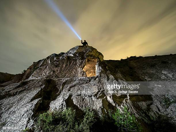 Man on a rock with a cave doing luminous signs of aid during the night