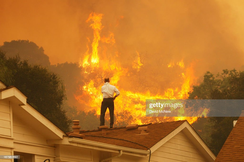 A man on a rooftop looks at approaching flames as the Springs fire continues to grow on May 3, 2013 near Camarillo, California. The wildfire has spread to more than 18,000 acres on day two and is 20 percent contained.