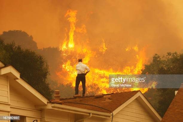 Man on a rooftop looks at approaching flames as the Springs fire continues to grow on May 3, 2013 near Camarillo, California. The wildfire has spread...