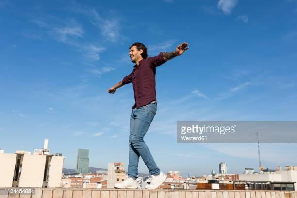 man on a rooftop terrace, balancing on a wall - un solo hombre fotografías e imágenes de stock
