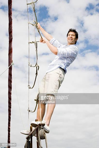 Mann auf Segelboot Seil Klettern die Leiter