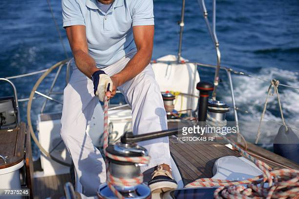 Man on a sailboat pulling a rope