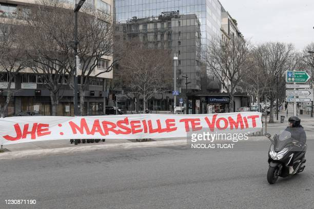 Man on a scooter looks over at a banner hung by Olympique de Marseille football club fans against the club's president Jacques-Henry Eyraud, that...