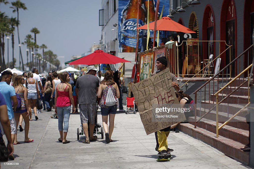 A man on a skateboard advertises his trade, getting paid to get kicked in the groin, on Independence Day weekend at Venice Beach on July 6, 2013 in Venice, California. An estimated 16 million people visit the famous beach city annually which is celebrating 108th birthday as of July 4.