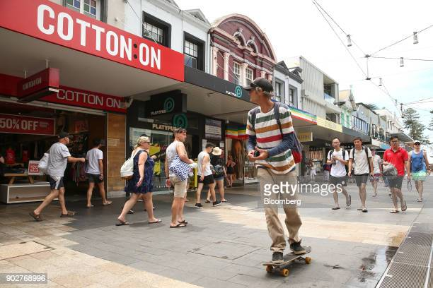 A man on a skateboard rides past as pedestrians walk past stores in the Manly Corso retail area in Sydney Australia on Friday Jan 5 2018 The...