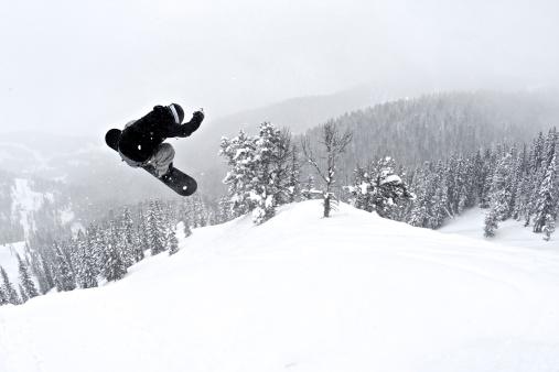 A man on a snowboard flies through the air after hitting a jump. - gettyimageskorea