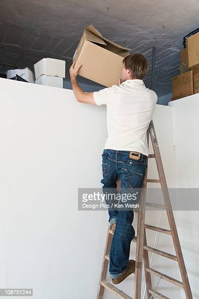 A Man On A Step Ladder Tidying Up The Attic