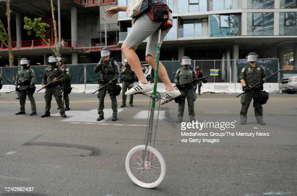 A man on a unicycle rides past Santa Clara County Sheriffs officers during a protest of the killing of George Floyd outside of San Jose City Hall in...