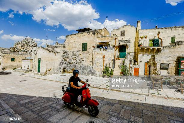 """Man on a Vespa scooter rides in the old town. Also named the city of stones, Movie set for movies as """"The Gospel according to Mattew"""" directed on..."""