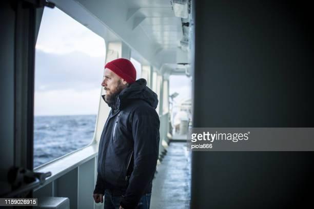 mann auf einem schiff, das das meer segelt - passagier wasserfahrzeug stock-fotos und bilder