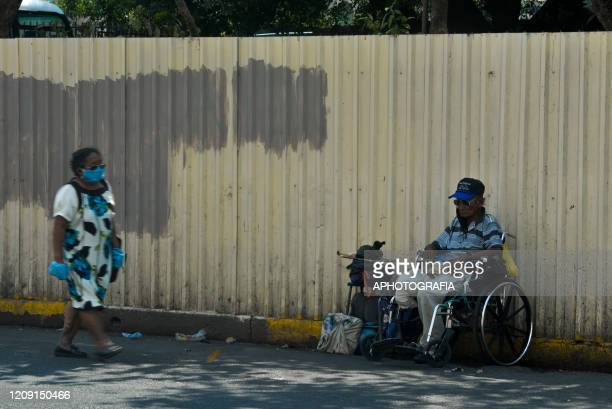 A man on a wheelchair watches as people pass by on April 2 2020 in San Salvador El Salvador On March 21st President Nayib Bukele declared a 30day...