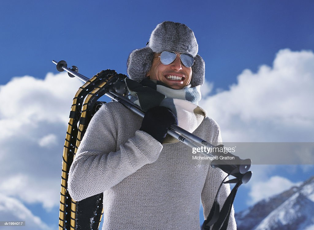Man on a Winter Vacation Holding Ski Poles and Wearing Sunglasses and a Deer Stalker : Stock Photo