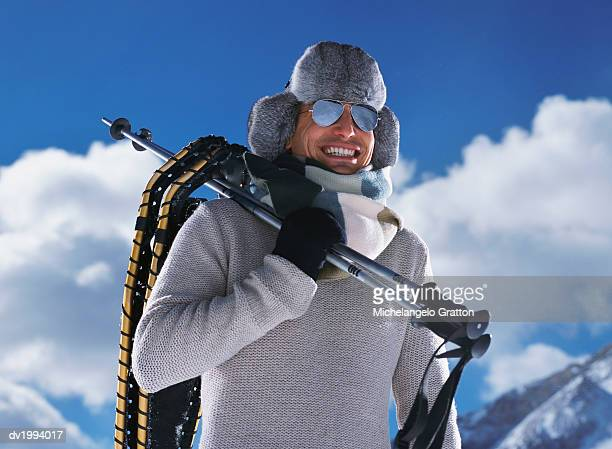 Man on a Winter Vacation Holding Ski Poles and Wearing Sunglasses and a Deer Stalker