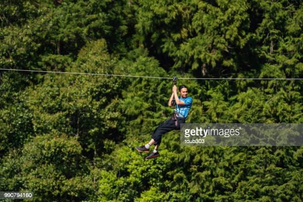 Homem em uma tirolesa voando através de um desfiladeiro florestal