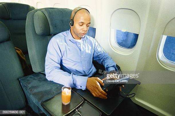 Man on airplane using handheld electronic device