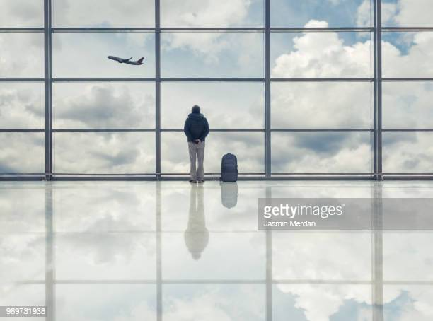 Man on airport looking at flying airplane