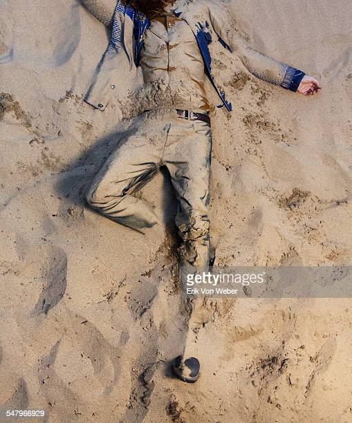 man on back shot from above buried in sand