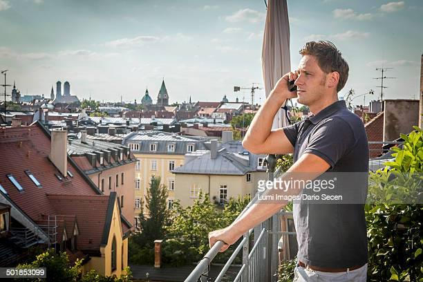 Man On Balcony Using Mobile Phone, Munich, Bavaria, Germany, Europe