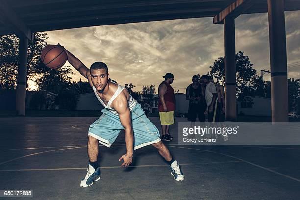man on basketball court bending forward holding basketball - rebote fotografías e imágenes de stock