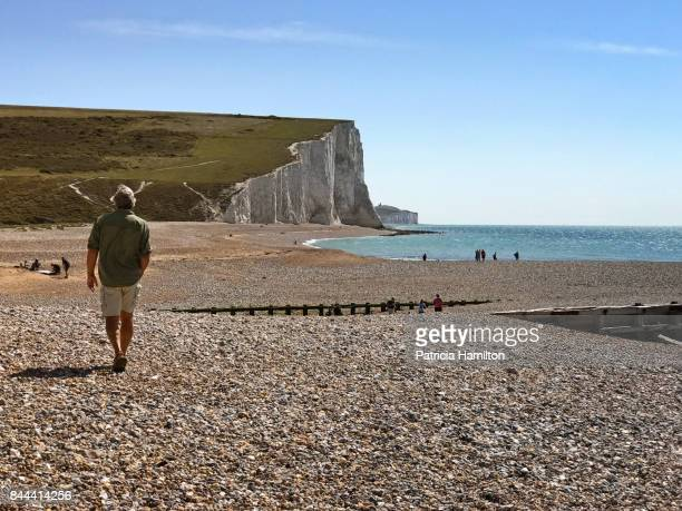 man on beach at cuckmere haven - english channel stock photos and pictures